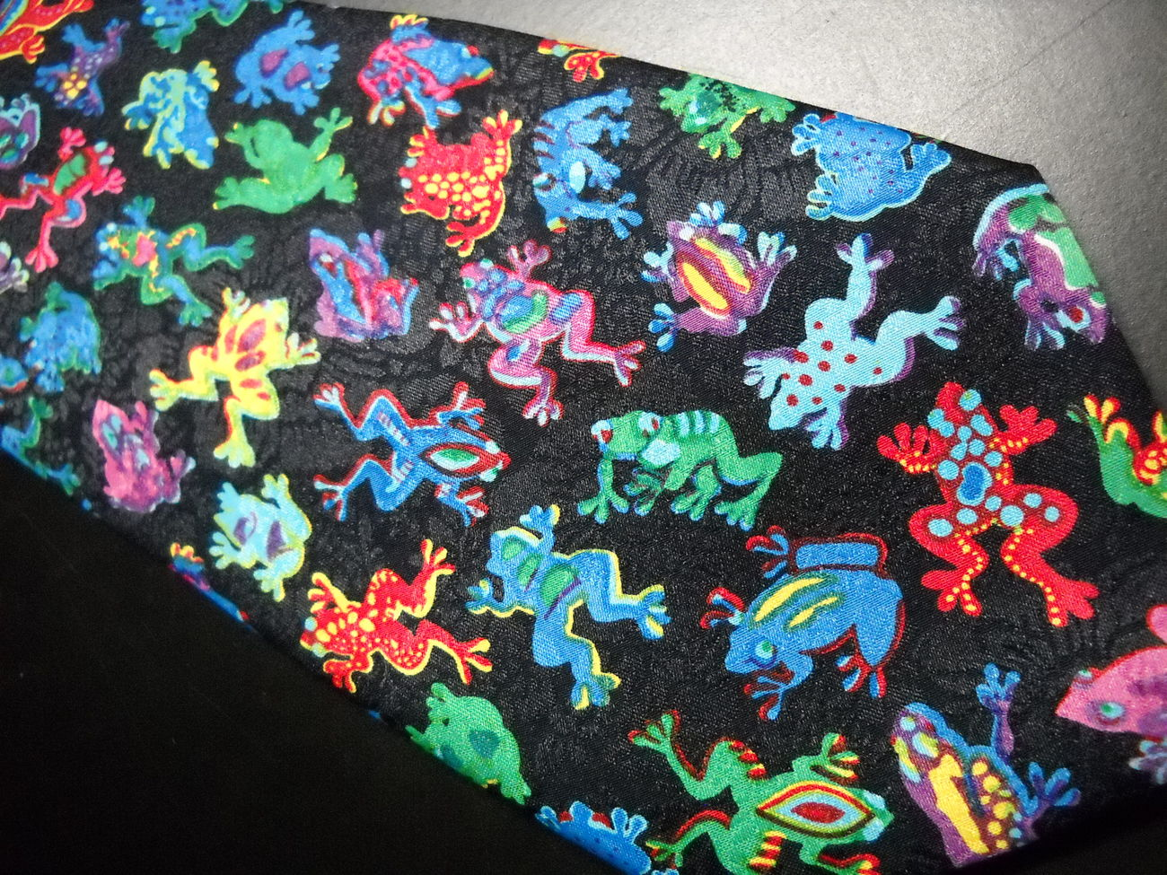 A Rogers Neck Tie Frogs Multiples of Brightly Colored Frogs on Black Background