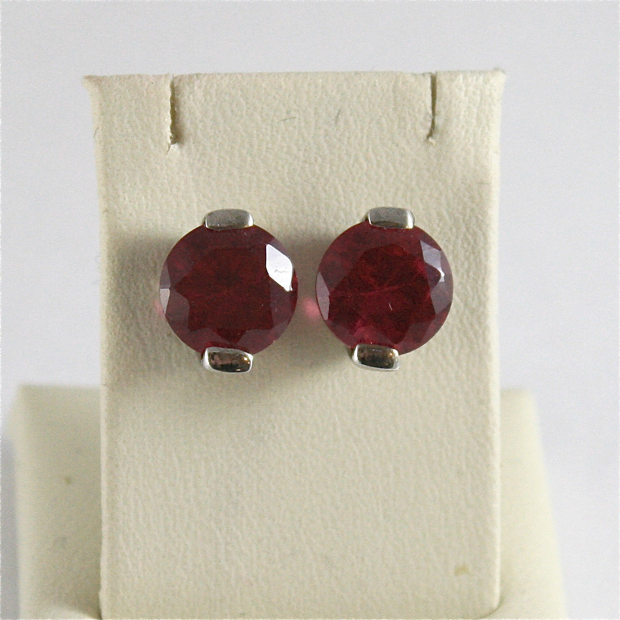.925 RHODIUM SILVER EARRINGS WITH RED FACETED CRYSTAL.