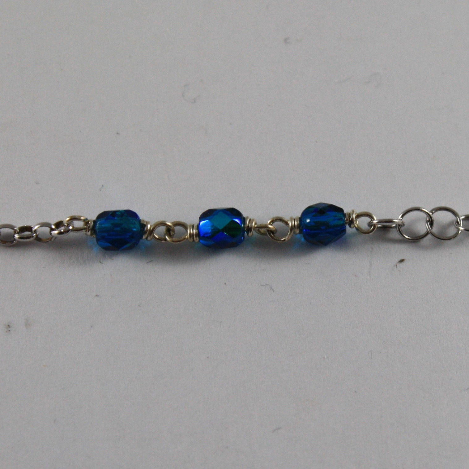 .925 SILVER RHODIUM NECKLACE WITH BLUE CRYSTALS AND LITTLE BOY SHAPED PENDANT