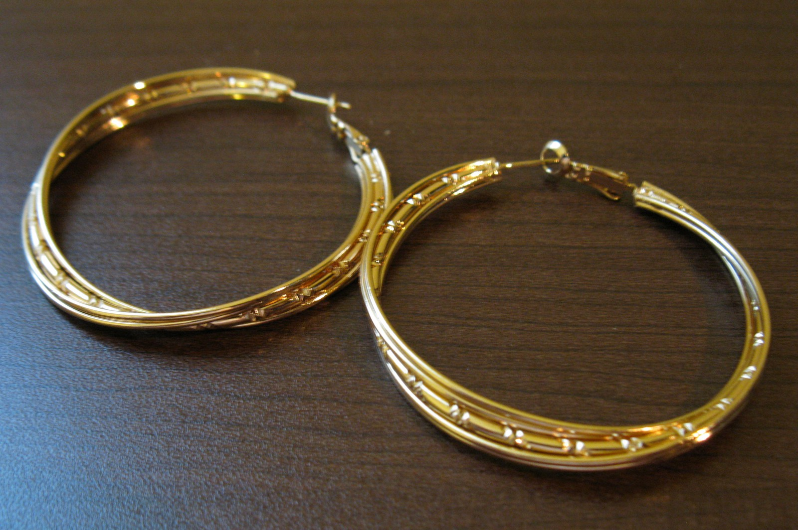 Perfect for summer outfits and more, these large 14K yellow gold hoop earrings for her feature a realistic bamboo design. The earrings are secured with snap-lock backs.