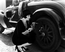 Dorothy Sebastian changing tire on vintage car 11x14 Photo - $14.99