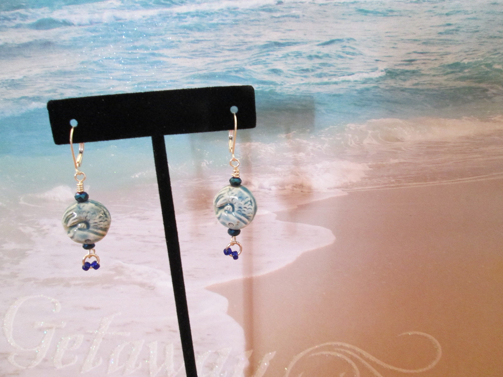 """I Sea You"".  The stones are variegated blue and white, with two smaller hanging"