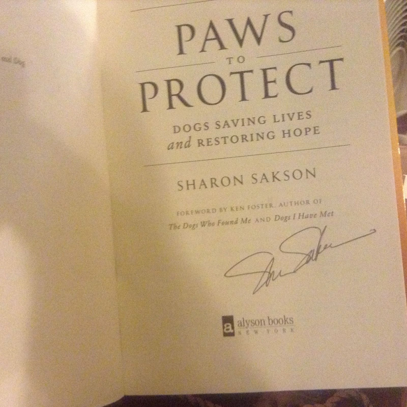 Paws to Protect : Dogs Saving Lives and Restoring Hope SIGNED by Sharon Sakson