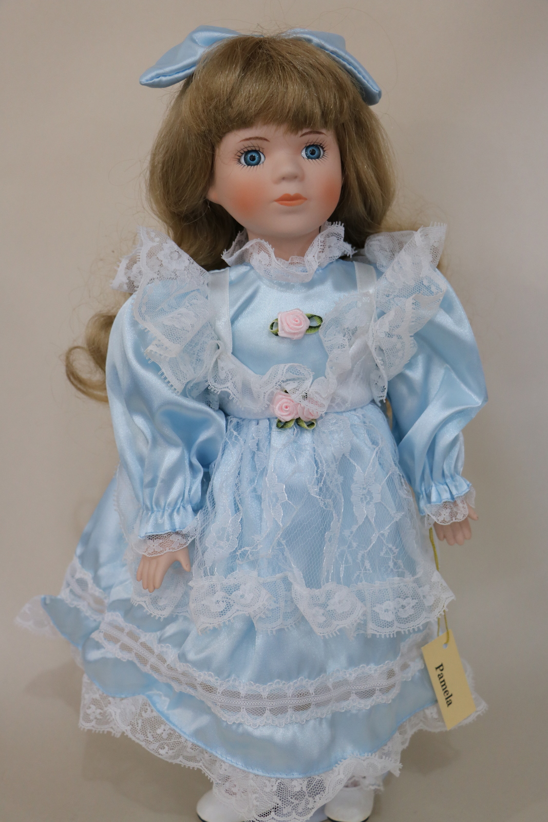 Porcelain Ceramic Doll with Long Blond hair and blue eyes wearing a Blue Dress