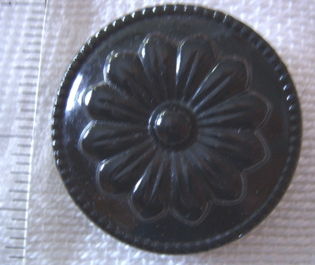 Large black floral celluloid button