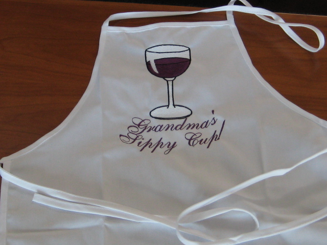 White adult apron with Grandma's Sippy Cup embroidered with wine glass