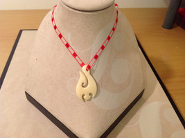 "Abstract indigenous necklace, plastic pendant, red threaded cord, 14"" long"