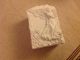 Angel trinket box  with pensive angel holding flower in garden
