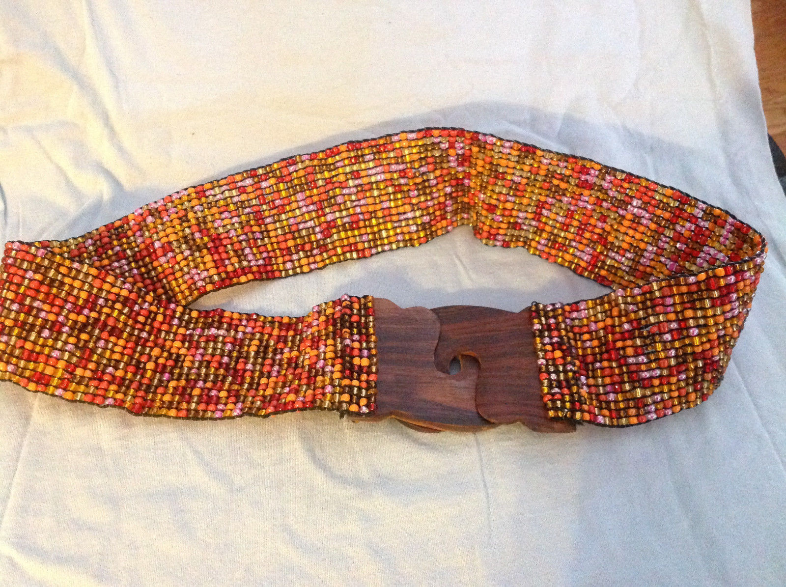 Beaded elastic multicolored belt with wood closure that slips together to close
