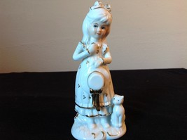 Ceramic Status of Girl White with Gold Covering Holding a Hat and Cat Sitting