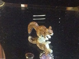 Ceramic miniature brown squirrel running with fluffy tail