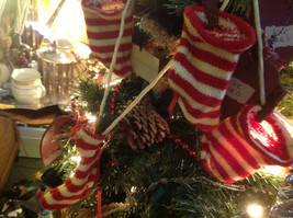 Five red white striped knitted stockings on washline with rusty clothespins image 1