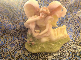 Gentle Angel holding a butterfly in repose in the garden image 1