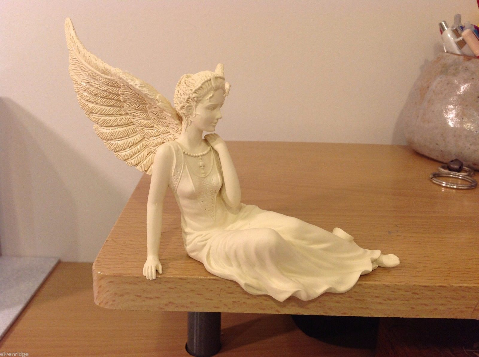 Graceful angel sitter girl with glitter wings flowing gown sitting reclined