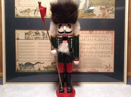 Green Russian Hat Wearing Nutcracker with Flag in Hand Ten and Half Inches Tall