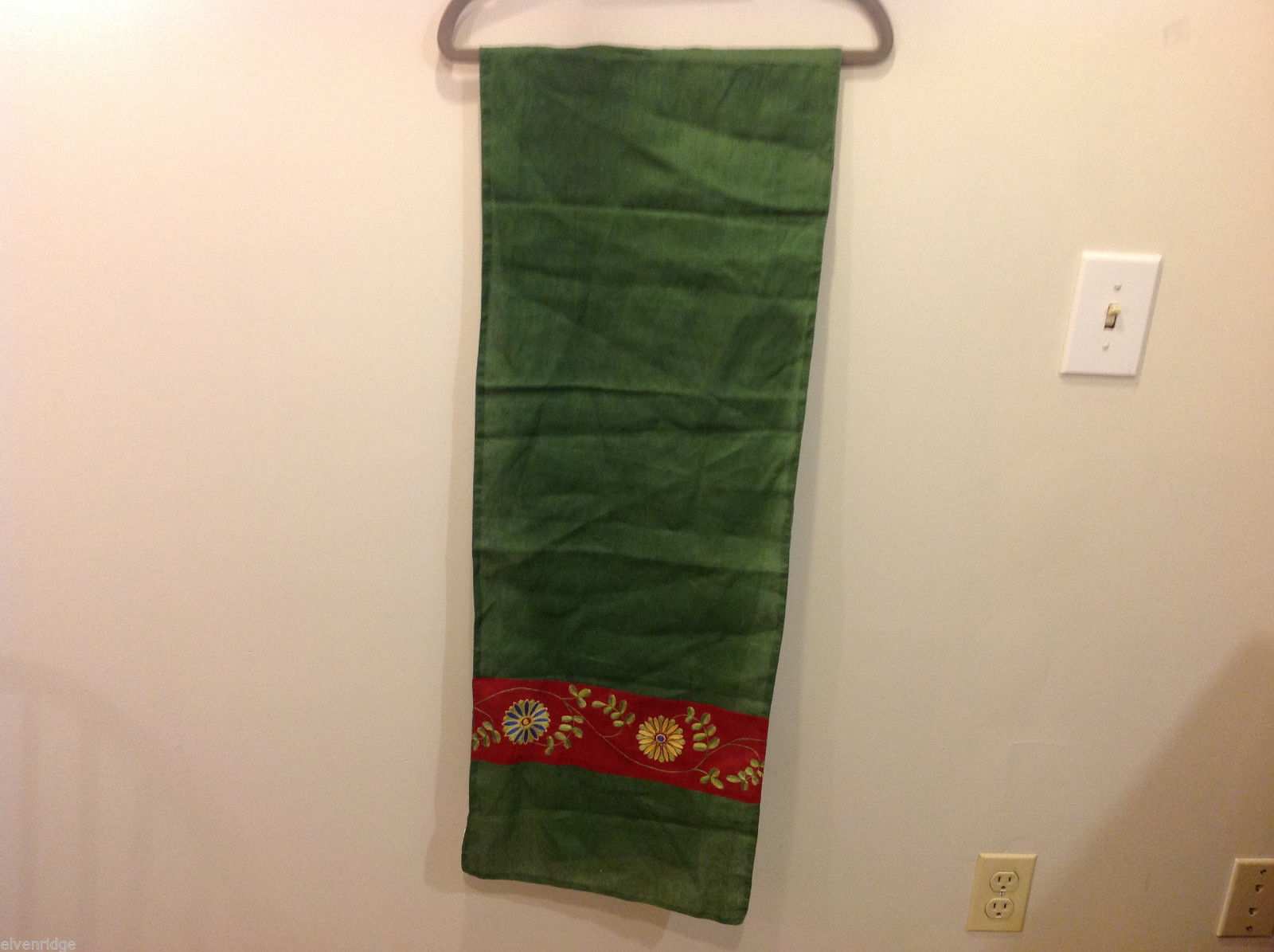 Green table runner with red stripes on both ends with floral design 100% cotton