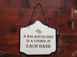 Metal Sign with Wording A balanced diet is a cookie in each hand Black and White