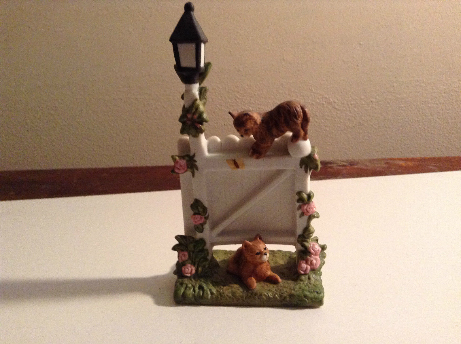 Playful Brown Porcelain Kittens Playing On White Fence with Light Pole Flowers
