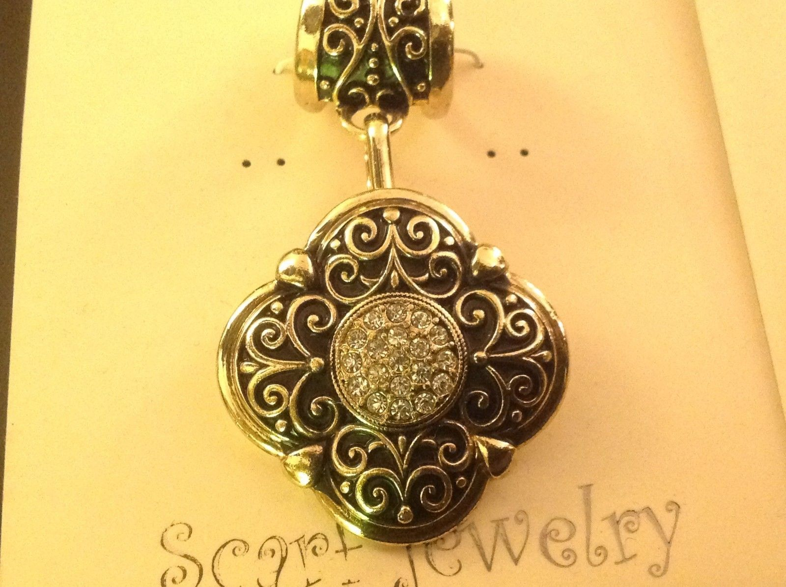 Scarf pendant gold tone enamel embossed relief and crystal studded oval