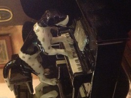 ceramic miniature dog black and white and spotted Pointer playing the piano