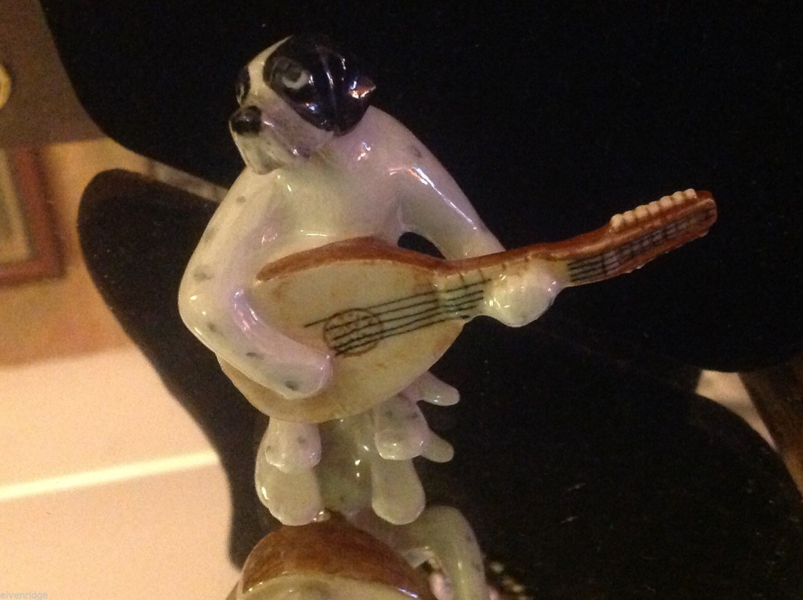 ceramic miniature dog black and white and spotted Pointer playing balalaika