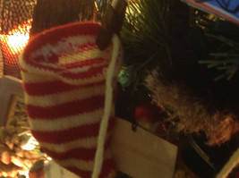 Five red white striped knitted stockings on washline with rusty clothespins image 6