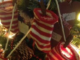 Five red white striped knitted stockings on washline with rusty clothespins image 8