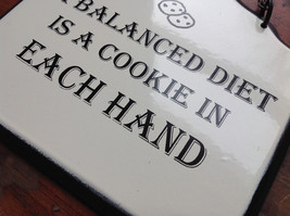 Metal Sign with Wording A balanced diet is a cookie in each hand Black and White image 4