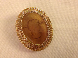 Beautiful gold toned cameo pin with filigree flourishes by Warner
