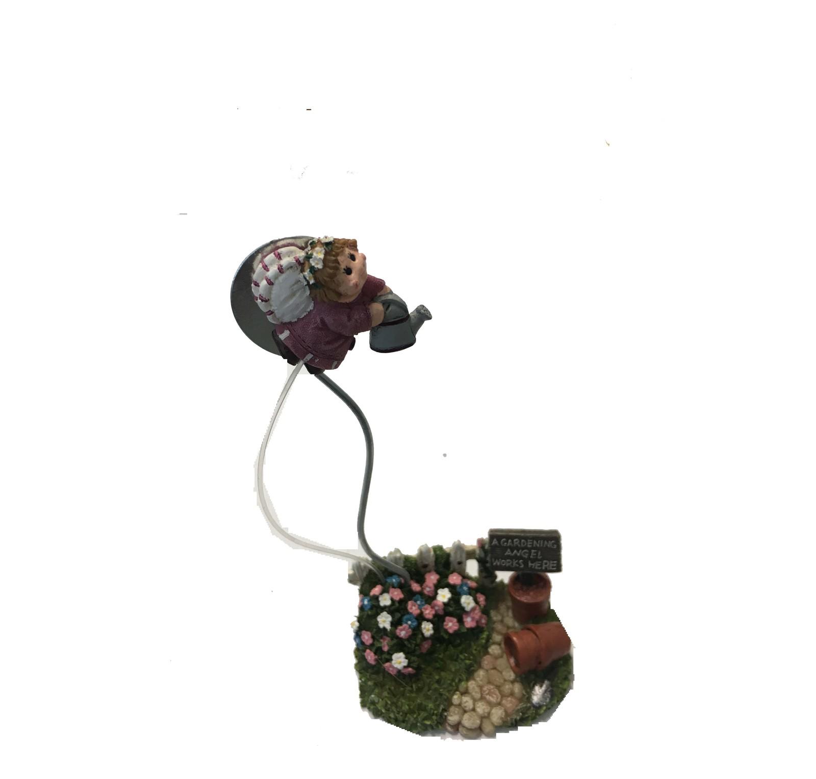 A gardening angel wirks here ceramic ornament