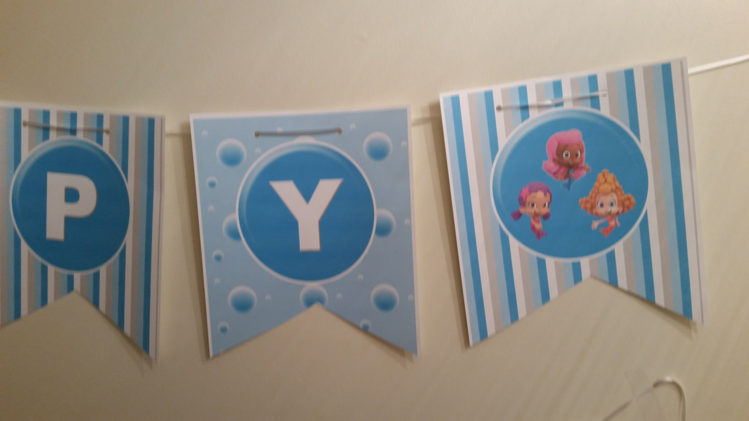 Bubble Guppies birthday banner in blue stripes and bubbles