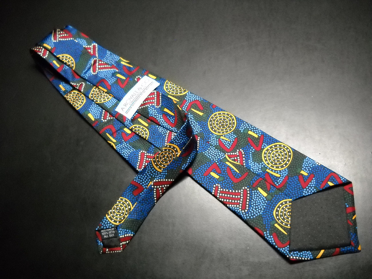 A Royale And Co Australian Neck Tie Hatch Bright Yellows Reds Hues of Blues Silk