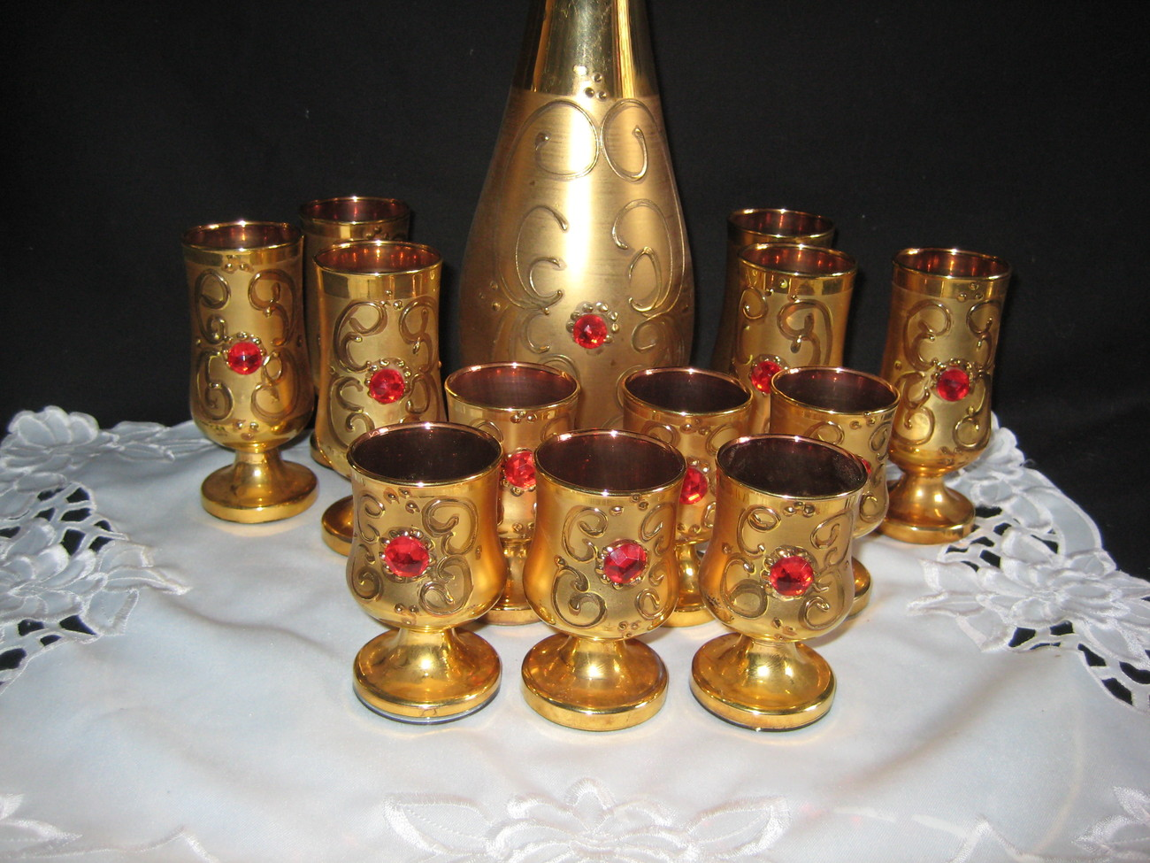 Antique gold decanter set with 12 glasses and pretty red sto