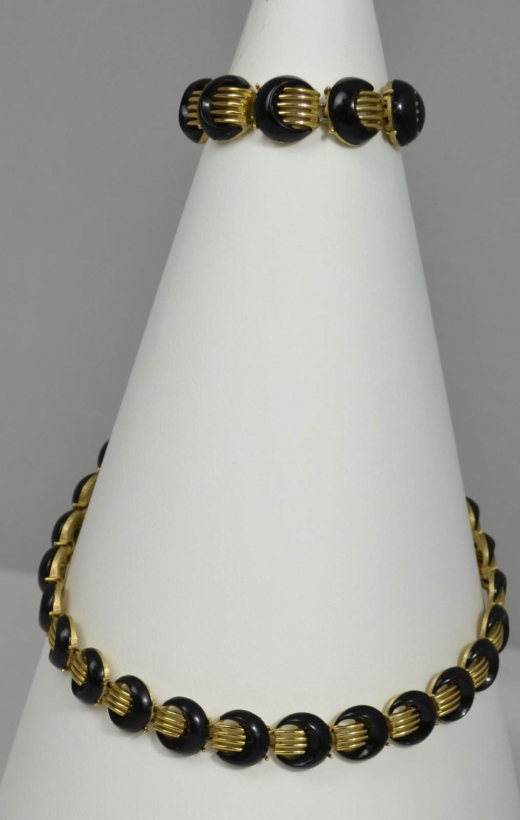 A set of curled bracelet and necklace with a black crescent