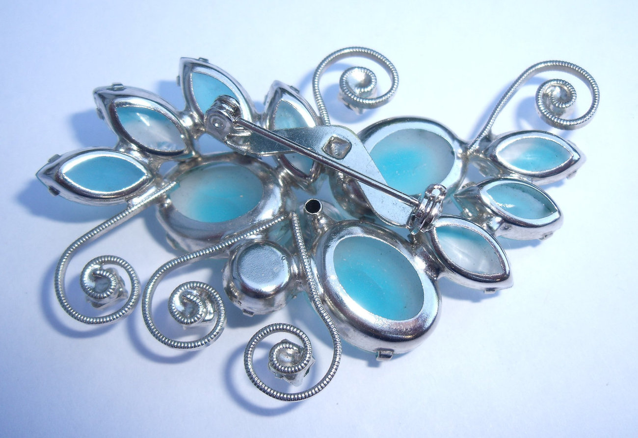 Frosted blue glass and rhinestone brooch with silver tone background