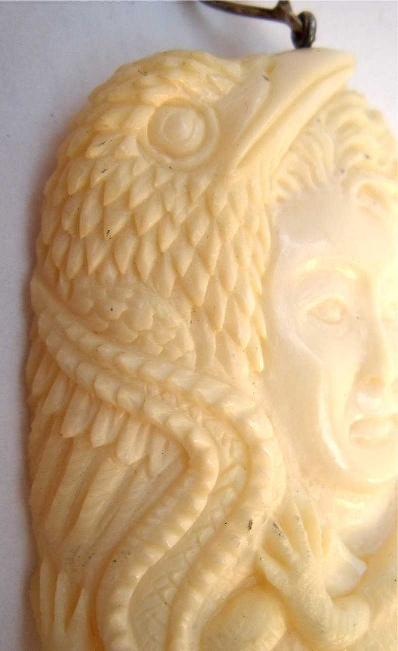 Carved bone fantasy pendant with face, bird and a crocodile