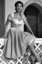 Yvonne De Carlo in Hotel Sahara Busty Full Length Pose on Set Seated on Wall 18x - $23.99