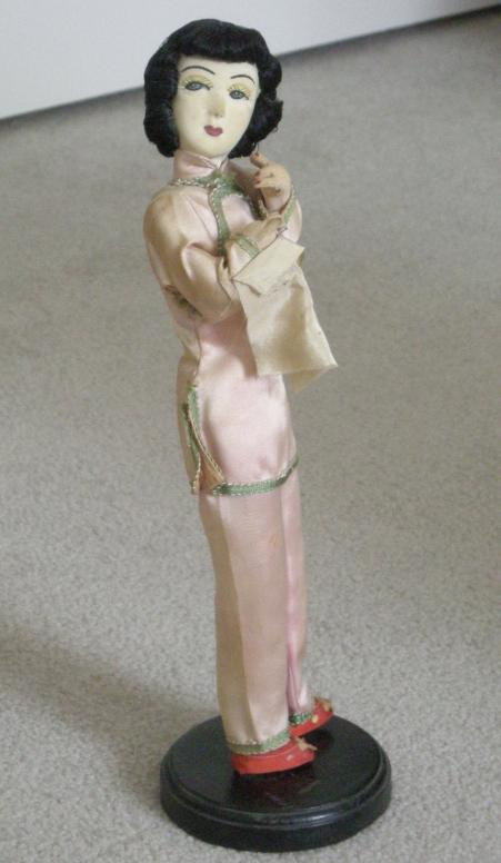Oriental doll on wooden stand