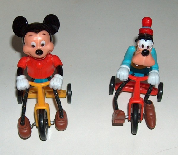 Mickey mouse and goofy on tricycle
