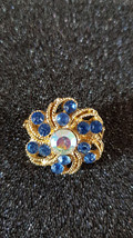 Brooch with ab crystal eye and dark blue crystals surrounding centre stone in go