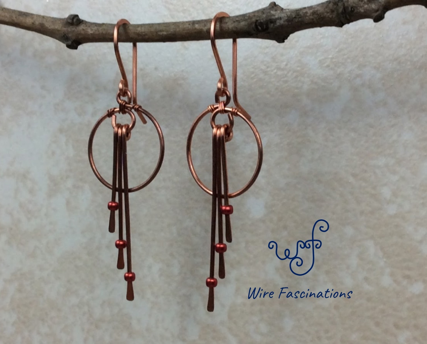 Handmade copper earrings: small hoops and three long dangles with red beads