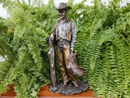 COWBOY HOLDING SADDLE LEANING AGAINST FENCE POLE VERONESE (WU73585A4) - $84.15