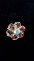Brooch with ab crystal eye and purple crystals surrounding centre stone in gold