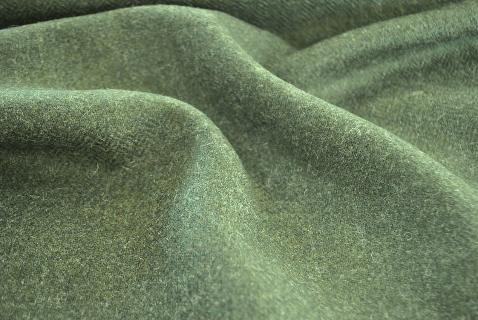 Tweed material by the metre or yard in green with subtle herringbone pattern