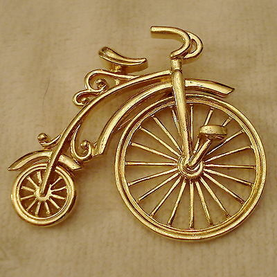 Primary image for Avon Big Wheel Bicycle Pin Bold Gold Tone Antique Spinning Wheel FUN VTG 1980s
