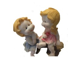 Decorative twin dolls in pink and blue on bench thumb200