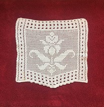 Vintage shield shape doily with large flower and intricate border detail.