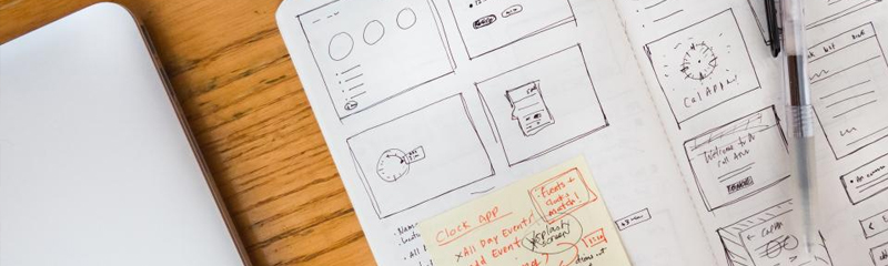 open notebook with drawings of UX design and a pen