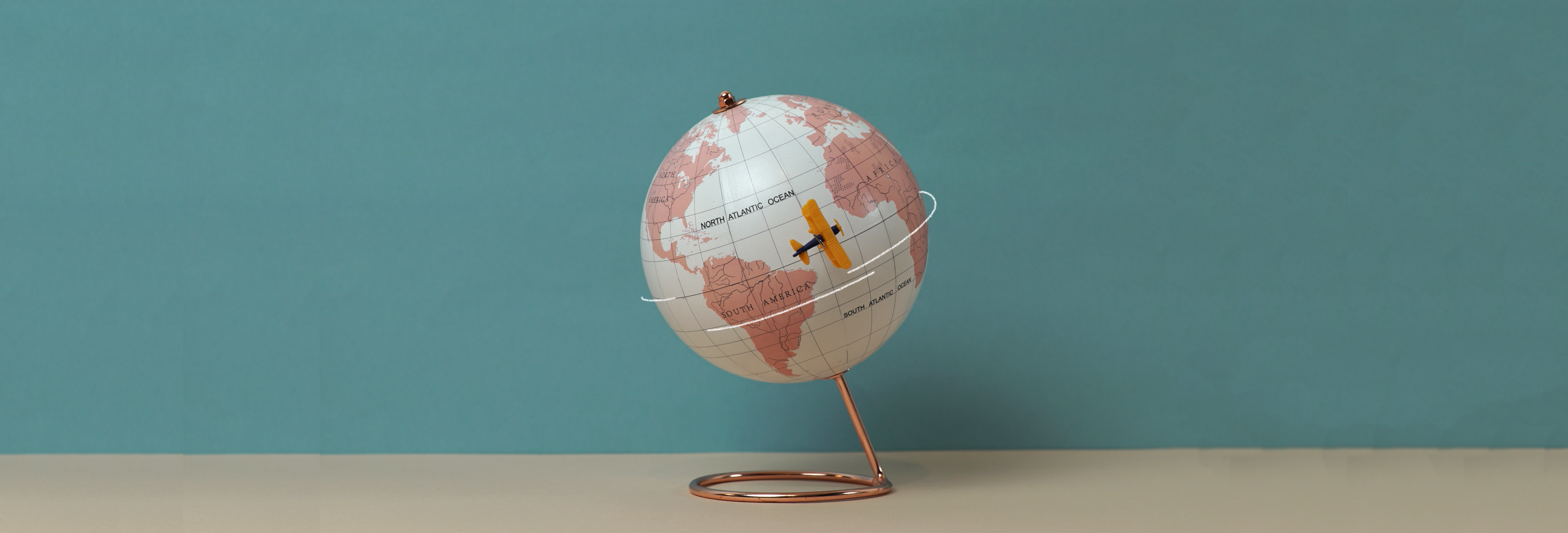 image of globe with toy airplane flying by
