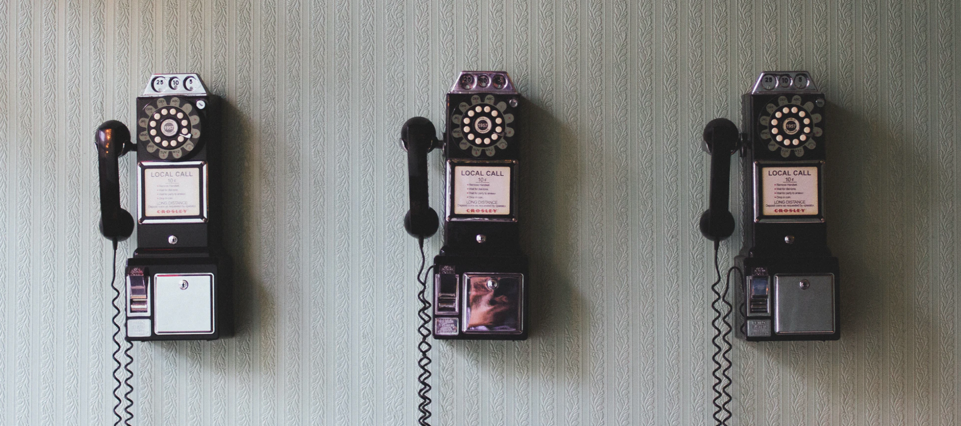 image of 3 early 19th century land line phones on wall